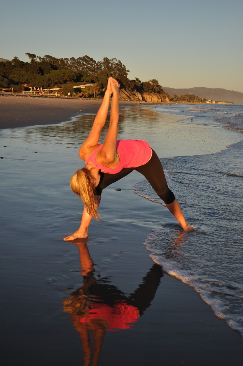 A woman stretching her arms behind her body on the beach