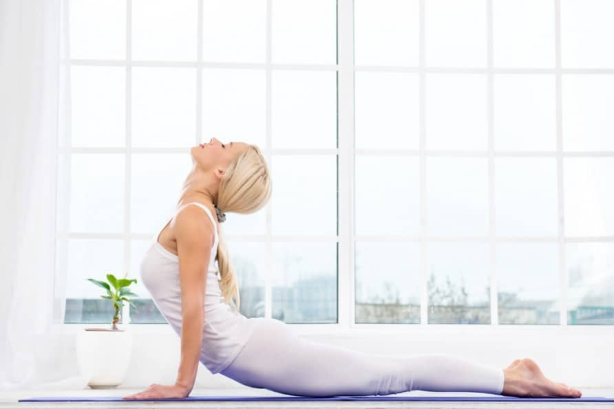 A woman on the ground stretching her neck and shoulder on a yoga matt