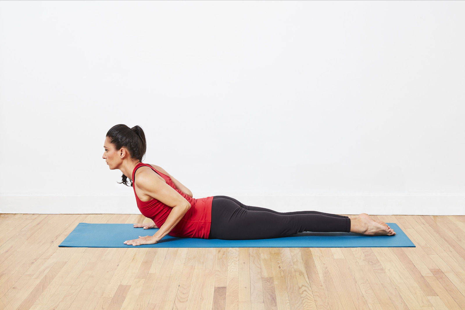 A woman on a yoga mat stretching her back